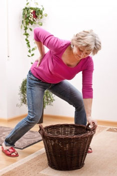 woman picking up basket in pain