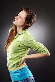 woman holding lower back in pain