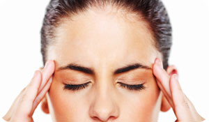 woman holding temples due to headache