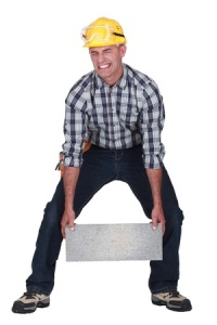 man lifting cinder block